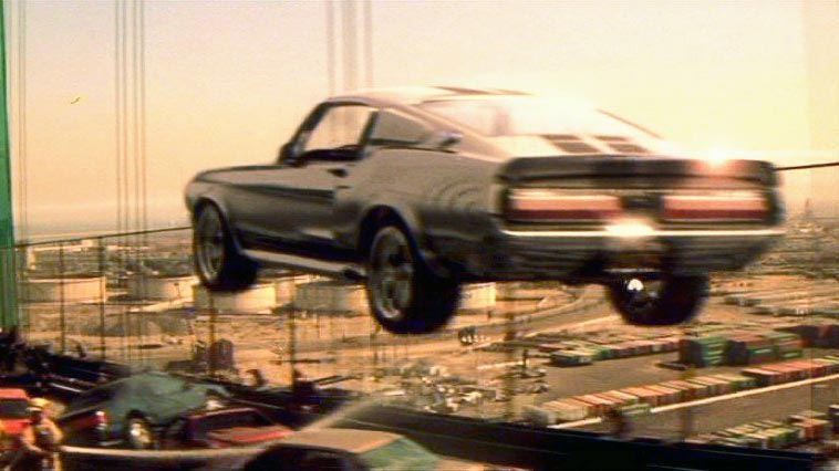 """When late great film critic Roger Ebert reviewed 2000's remake of the 1974 cult classic, he got the model of the hero car wrong but gave the movie props nonetheless; that's a pretty impressive feat, considering the original movie's final chase crunched gears and burned rubber for over half an hour. The new one does it justice, though, thanks to the fact that Cage mostly drove Eleanor himself and the fantastic clutch poppin', gear lever slammin', tach needle pingin' final stunt, where Cage's Memphis Raines clears an entire traffic jam in a single bound. And outpaces a chopper (impressive, even though it's only """"an Astar, sir, not an Apache""""). And navigates the streets of downtown LA… backwards, with enough time to smile and wave."""