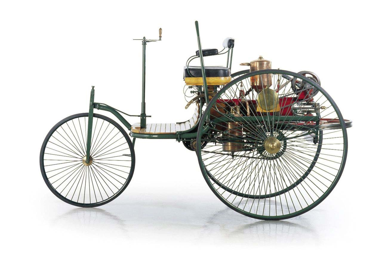 While there were other contraptions that could claim to be the first car, Karl Benz's invention was the first automobile in that it was designed from the ground up to be powered by an engine. The three-wheeled motorwagen boasted tiller steering, wagon-style wheels, and a single-cylinder four-stroke engine that produced anywhere from two-thirds of a horsepower to nine-tenths of a horsepower. The burnout was clearly yet to be invented. Benz's wife Bertha is often overlooked in the story of the automobile, but she was the first to travel any distance in her husband's invention (which her money had backed), as well as coming up with brake linings and fuel stops along the way. The automobile was here, and the first road trip had happened almost immediately.