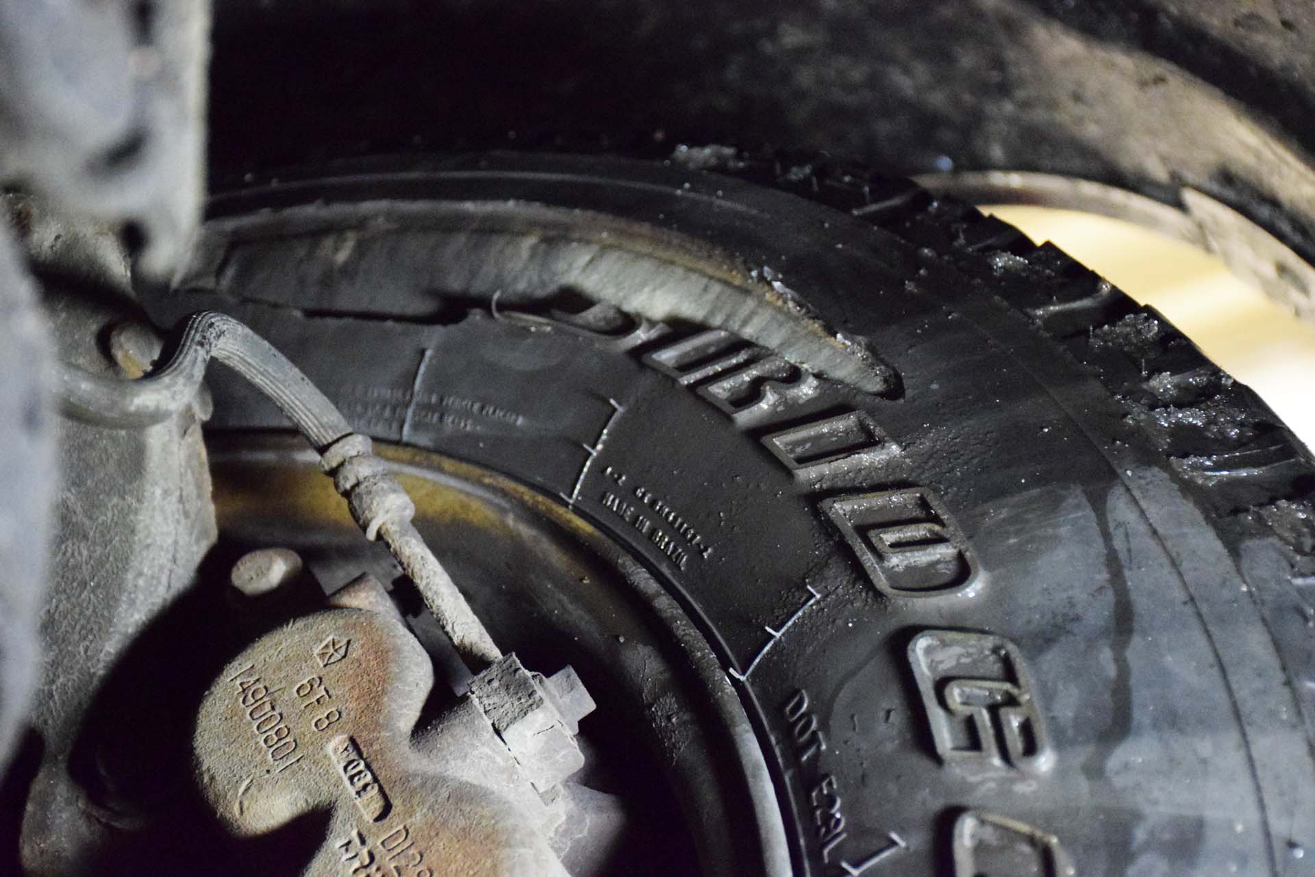 Your tires take a lot of abuse, and not all tire damage results in a flat tire, right away. In this photo, the tire has lost a portion of its sidewall—likely as a result of contact with a sharp rock in an off-road setting. Dangerously, this damage is on the inner tire sidewall, so it's virtually invisible to the driver. Still holding air, the driver of this vehicle may never know that he has a severely damaged tire. The white stuff inside of the slit is the tire's carcass, which you're not supposed to be able to see. Remember to have a mechanic inspect your tires regularly, perhaps while you're in for an oil change or tune-up.