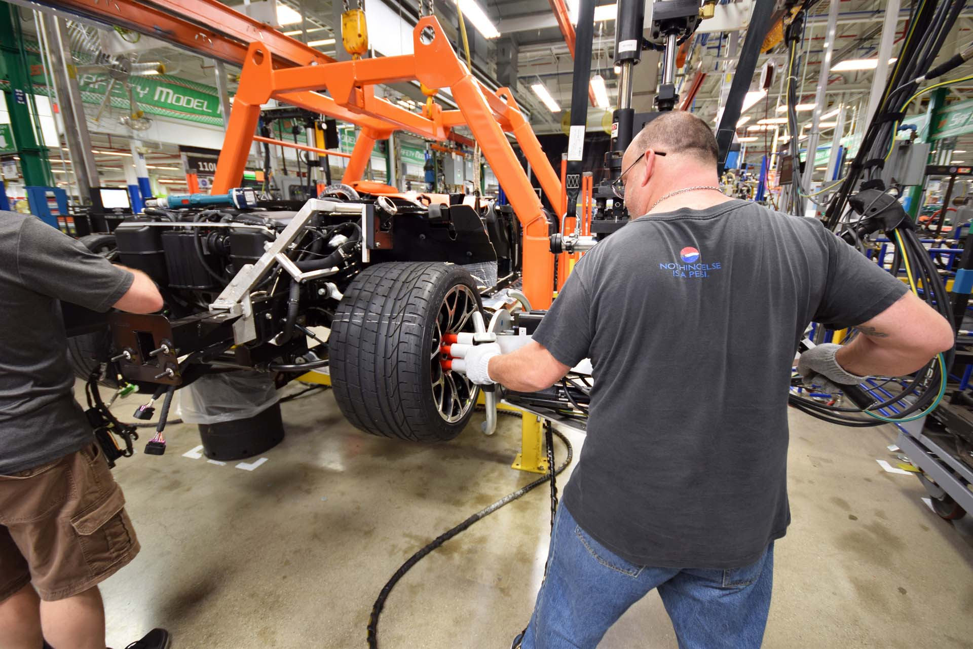 "With the brakes installed, this worker uses a special tool called a ""multi"" to fasten all six lug nuts down, precisely and simultaneously for a perfect fit. Later, he'll ensure the tires are inflated to the proper specifications before the car moves to its next station."