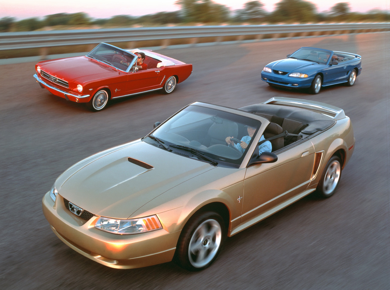 Three different generations of Ford Mustang convertibles from 1965, 1994 and 1999.