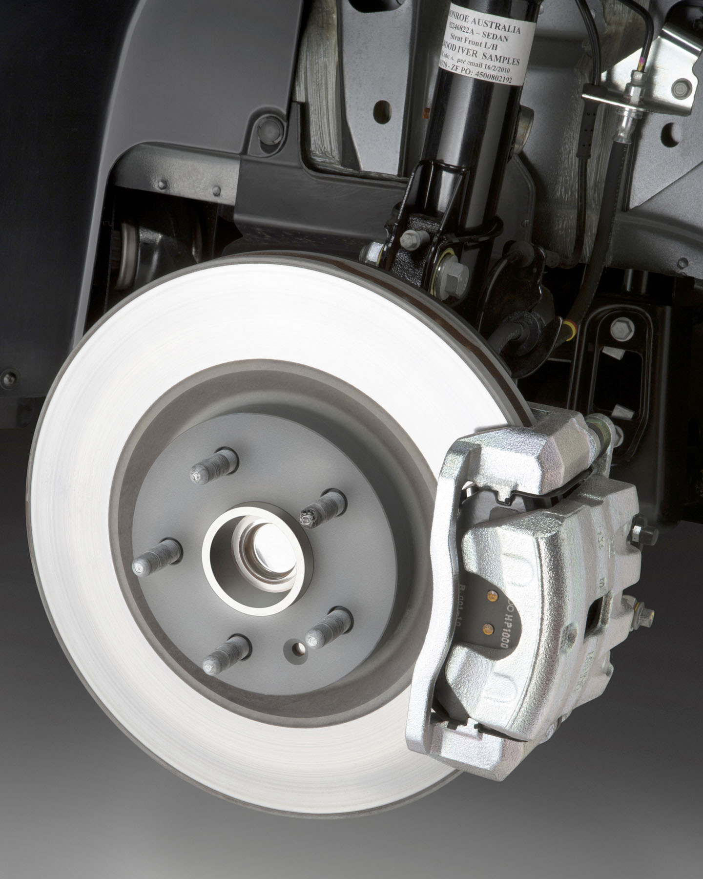 Here's a disc brake system, naked. The round, shiny bit is the brake disc or rotor. The assembly covering the front of it is the caliper. The pads, which create friction for stopping, are inside, between the body of the caliper and the brake disc. Look closely, and you can see a little bit of text printed on them. See the threaded posts sticking out?  The car's wheel bolts to those. The wheel and the brake disc spin as you drive, the caliper and pads don't. In a car with four-wheel disc brakes, there's a similar setup just behind each of the car's wheels.
