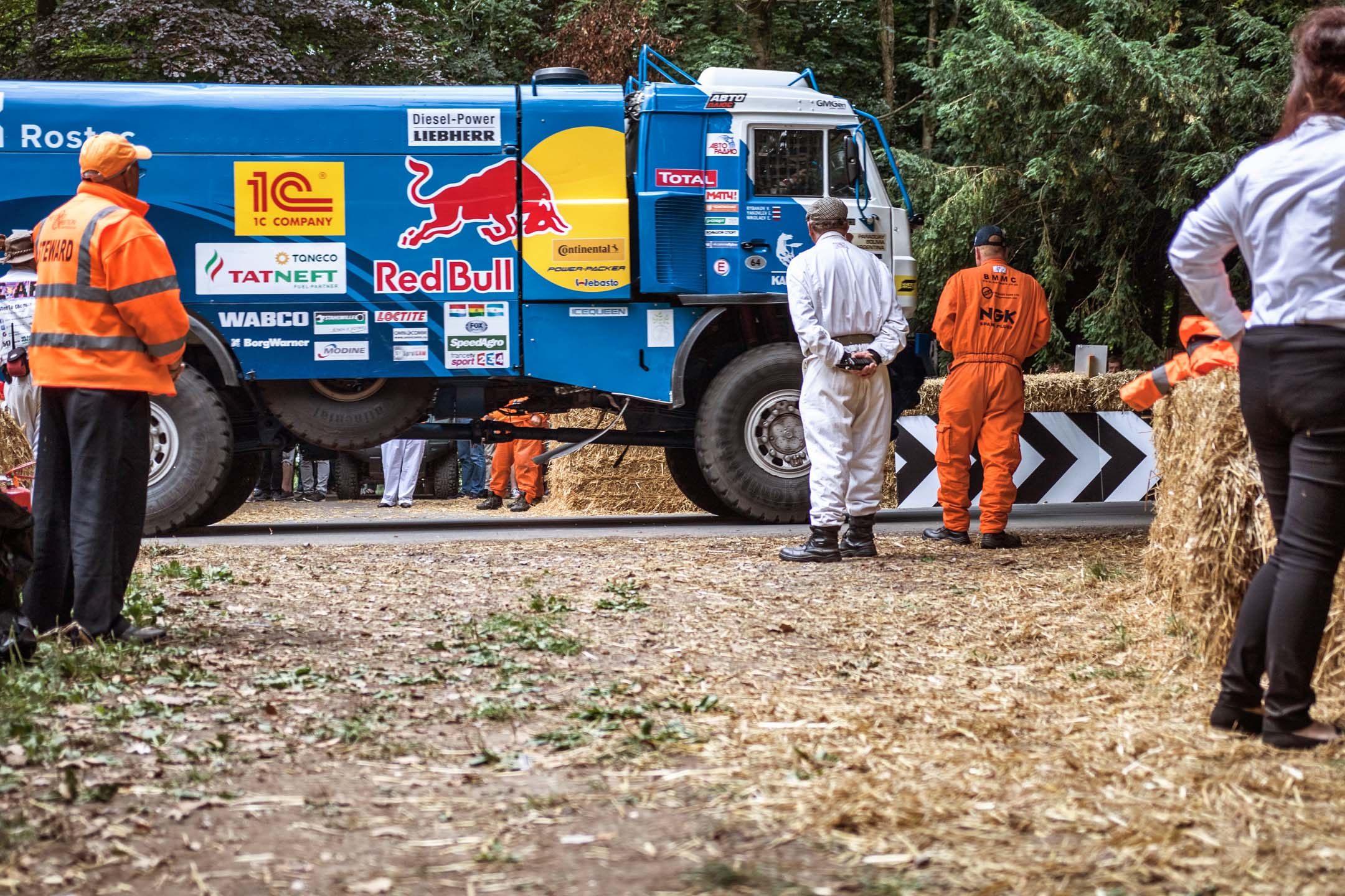 At the entry corner near the famously unforgiving flint wall, a leviathan appears. Intended for Dakar desert racing, this Red Bull-liveried truck appears in a whoosh of turbodiesel fury, then vanishes around the corner, chasing the finish line.